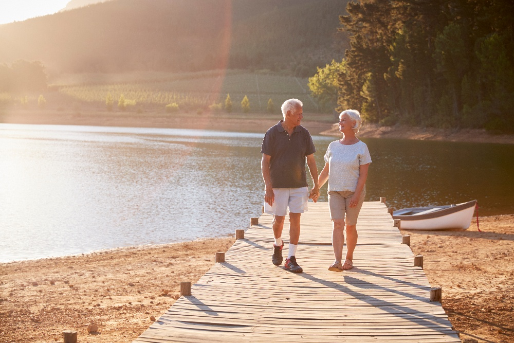 romantic-senior-couple-walking-on-wooden-jetty-by--M6ENCT5 (1)-1